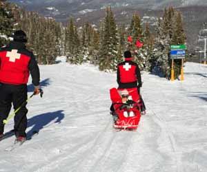 Ski Patrol Taking Injured Skier Down the Mountain in a Sled