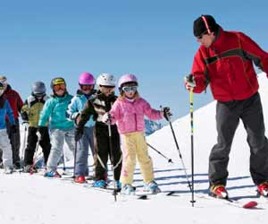 Ski Instructor Leading Youth Students during Ski School Lesson