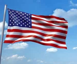 American flag fluttering in wind against blue sky
