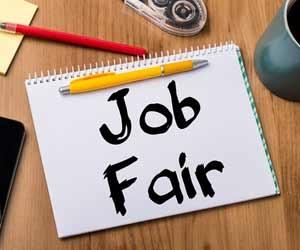 Note on desk with job fair written in black marker