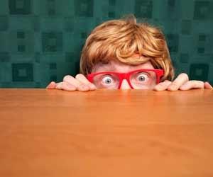 Scared boy in glasses hides behind a desk