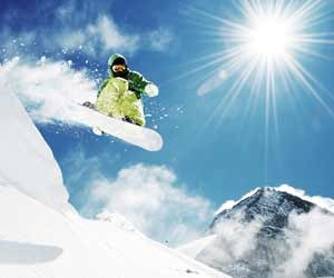 Snowboarder catching air off of natural jump with mountain in background