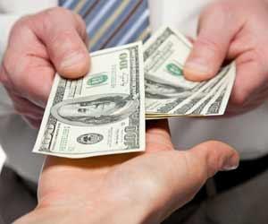 Boss hands over cash to open hands of employee