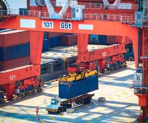 Longshoreman Operates Crane to Unload Cargo Ship at Port