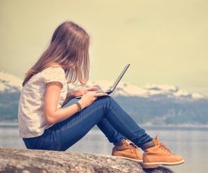 Freelance writer working on laptop on rock next to mountain lake