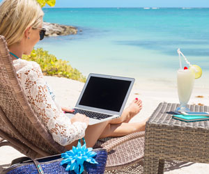 Woman on tropical beach working from her laptop sipping a fancy drink.