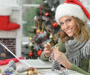 Woman wearing Santa hat while sitting by laptop during holidays